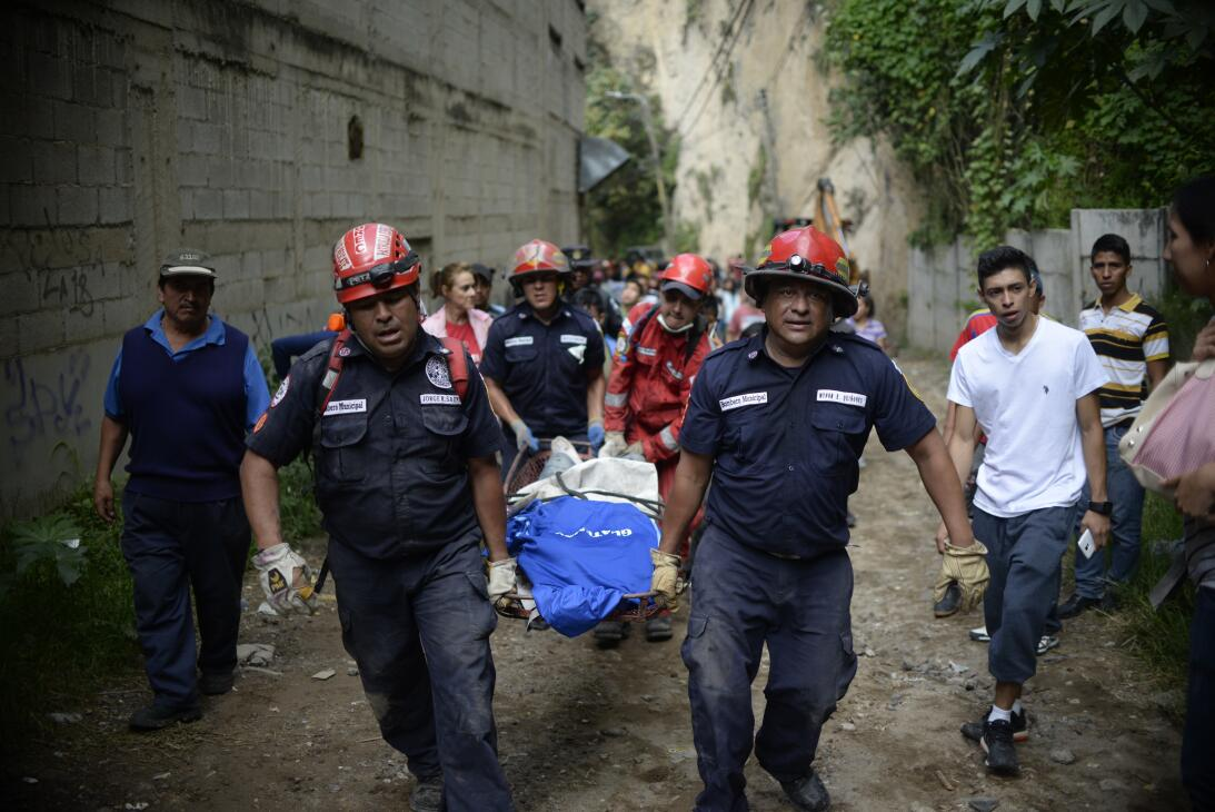 Rescuers carry a victim after a landslide at Cambray village, in Santa C...