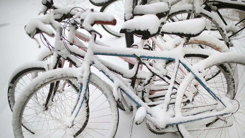 La nieve cubre las bicicletas estacionadas cerca del campus de la Univer...