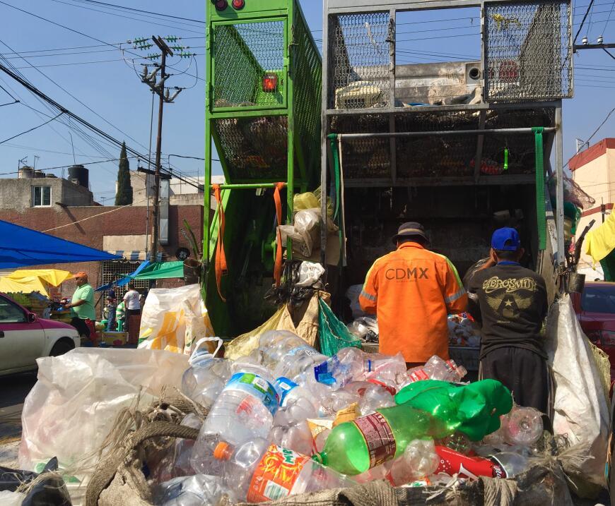 En una calle de la Ciudad de México, voluntarios en un camión de basura...