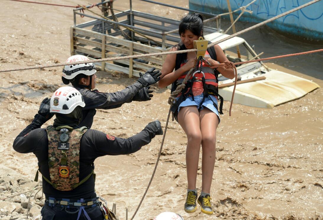 Bomberos ayudan a una mujer que quedó aislada por el agua en el distrist...
