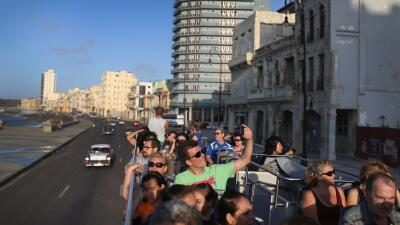 Un grupo de visitantes extranjeros recorre el malecón de La Haban...