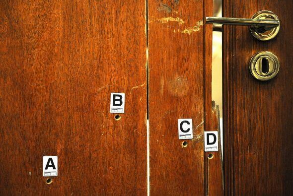 La puerta tiene cuatro agujeros de bala y las marcas de impactos produci...