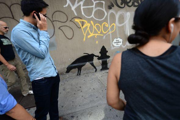 La gente mira sorprendida el arte graffiti callejero del artista brit&aa...