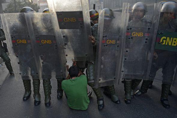 Un manifestante se sienta en el suelo frente a la Guardia Nacional. Los...