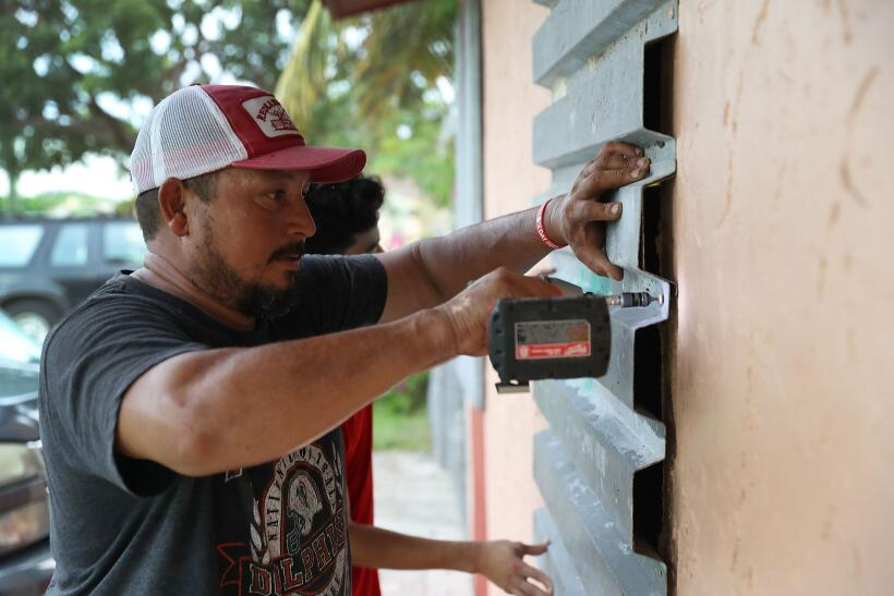 Un residente Homestead, al sur de Miami, protege las ventanas de su casa.