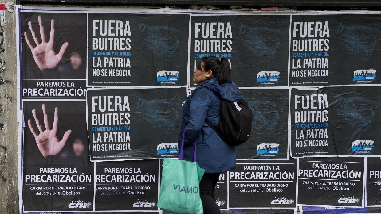 Una mujer pasea delante de carteles contra fondos buitre en Buenos Aires