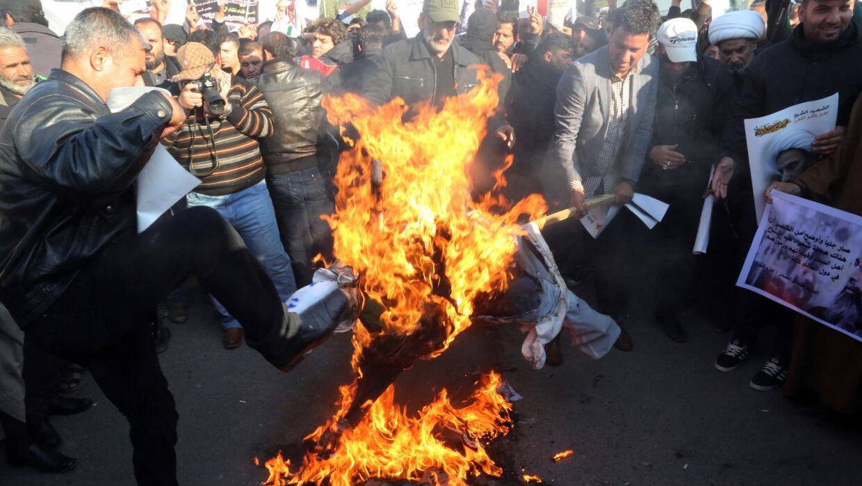Manifestantes queman una foto del rey de Arabia Saudita en Bagdad.