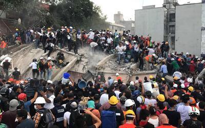Una multitud de rescatistas y voluntarios buscan a sobrevivientes de un...