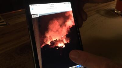Darryl Pridmore muestra una foto en su celular que capturó el fuego detr...
