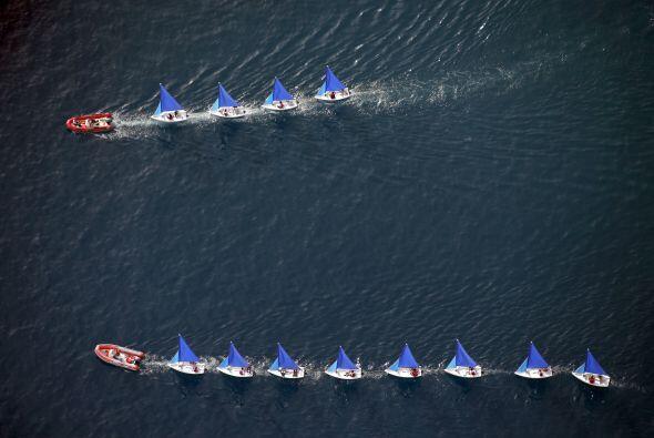 Una fotografía aérea de barcos de vela en una fila en el océano cerca de...