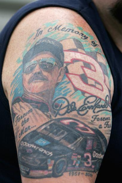 Un fanático con un tatuaje de Dale Earnhardt en su brazo mira la clasifi...