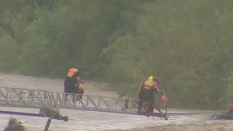 Rescatistas auxilian a un conductor atrapado en las inundaciones.