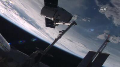 En esta imagen de NASA TV, la cápsula Dragon de SpaceX arriba a l...
