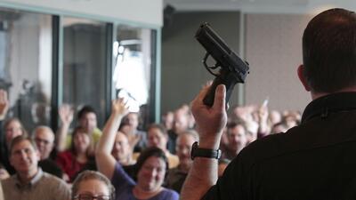 Un instructor de armas de fuego dictando un taller a más de 200 profesor...