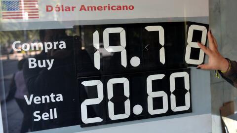 El tipo de cambio es mostrado en una de las vitrinas de un banco de  la...