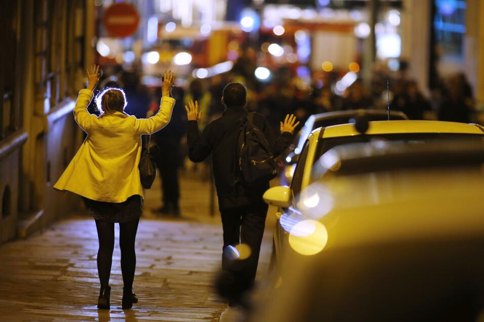 Peatones levantan sus manos para mostrar sus manos mientras caminan haci...