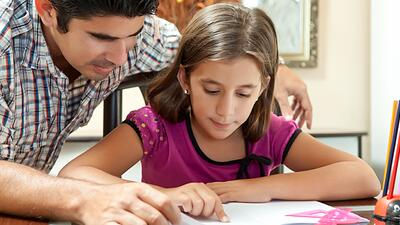 Dad helps daughter with homework.