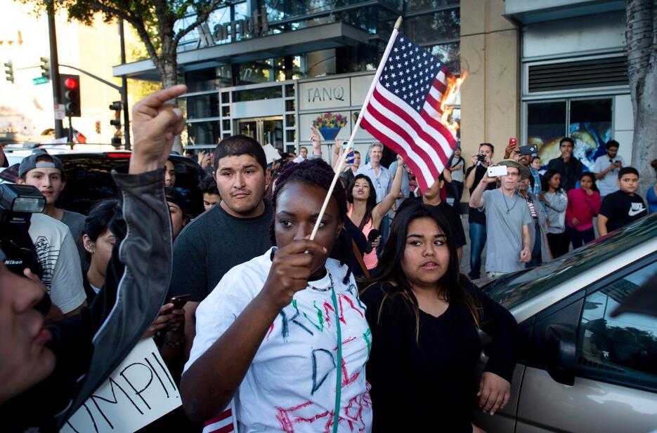 Una joven anti-Trump quema una bandera de EEUU en San José, California