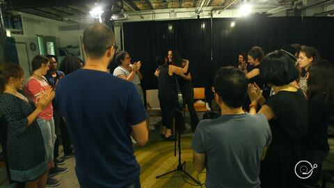 Refugees and immigrants come together to sing an improvised song with Eleni