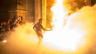 Manifestantes indignados por Ayotzinapa prenden fuego a la puerta de Pal...
