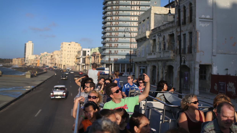 Un grupo de visitantes extranjeros recorre el malecón de La Habana a bor...