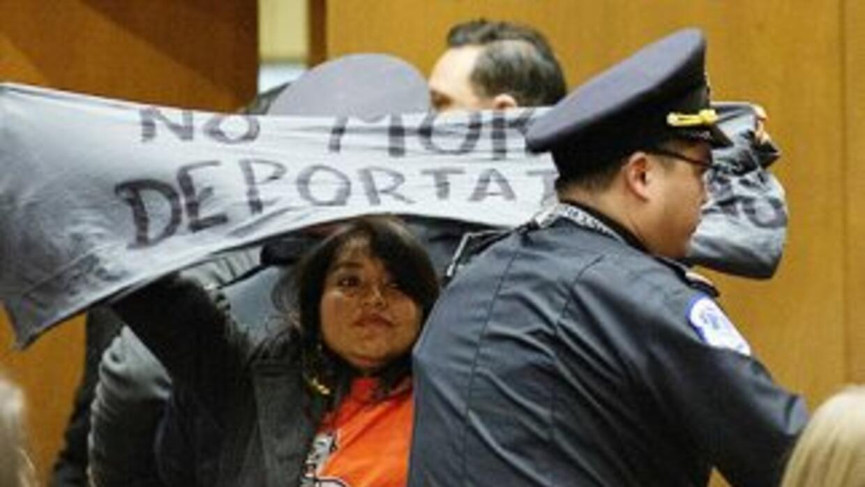 """Un manifestante levanta una manta con la leyenda """"No more deportations""""..."""