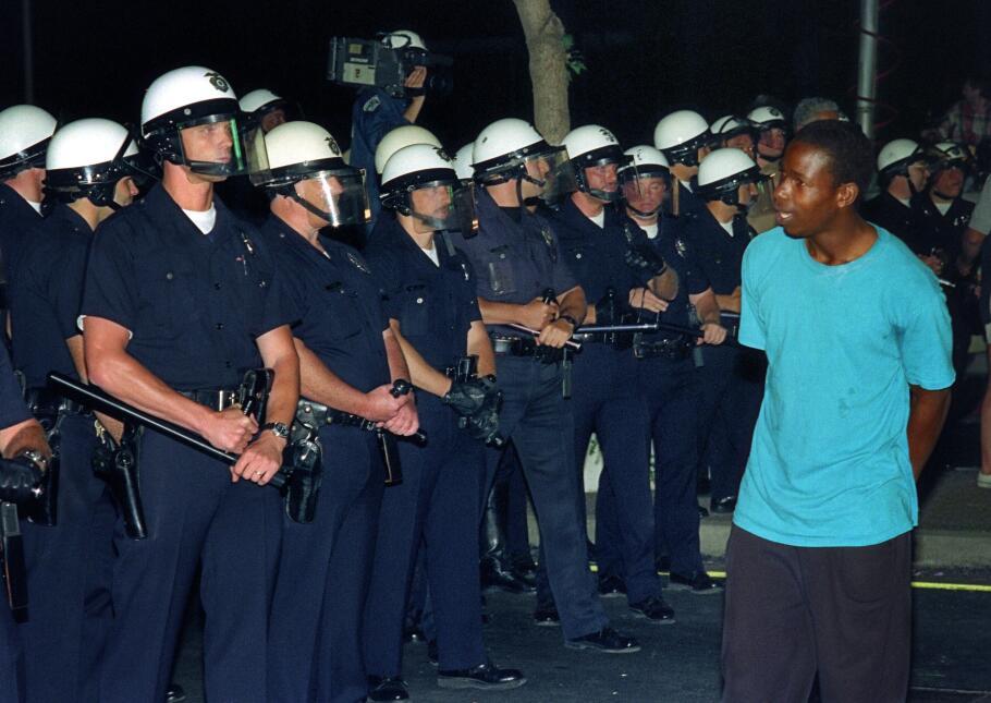 Un joven afroamericano camina frente a policías angelinos.