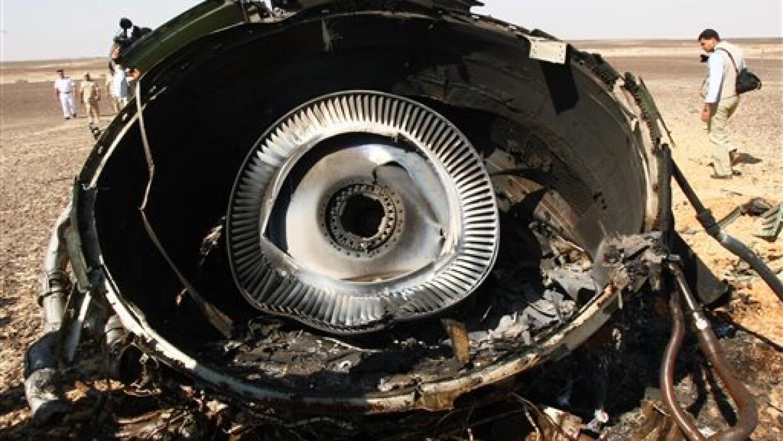 Expertos militares egipcios examinan una pieza del motor del avión ruso.
