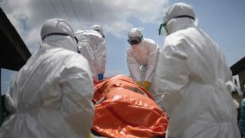 Trabajadores de salud en Liberia retiran el cuerpo de una mujer, víctima...