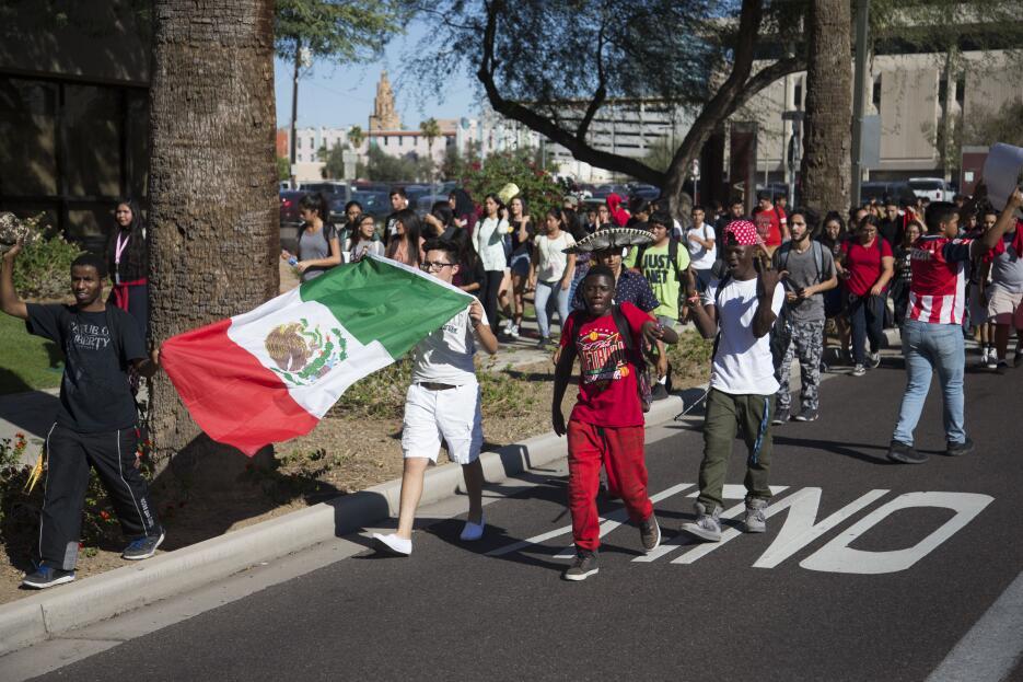 Con banderas mexicanas y sombreros de Mariachi, los estudiantes latinos...