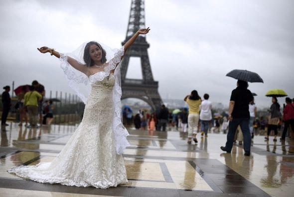 Una novia posa bajo la lluvia en el Trocadero, frente a la Torre Eiffel,...