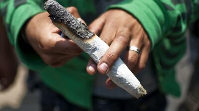 Un hombre enciende marihuana durante una manifestación.