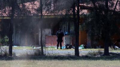 Policías buscan evidencia en rancho en Tanhuato donde hombres se ocultaron.